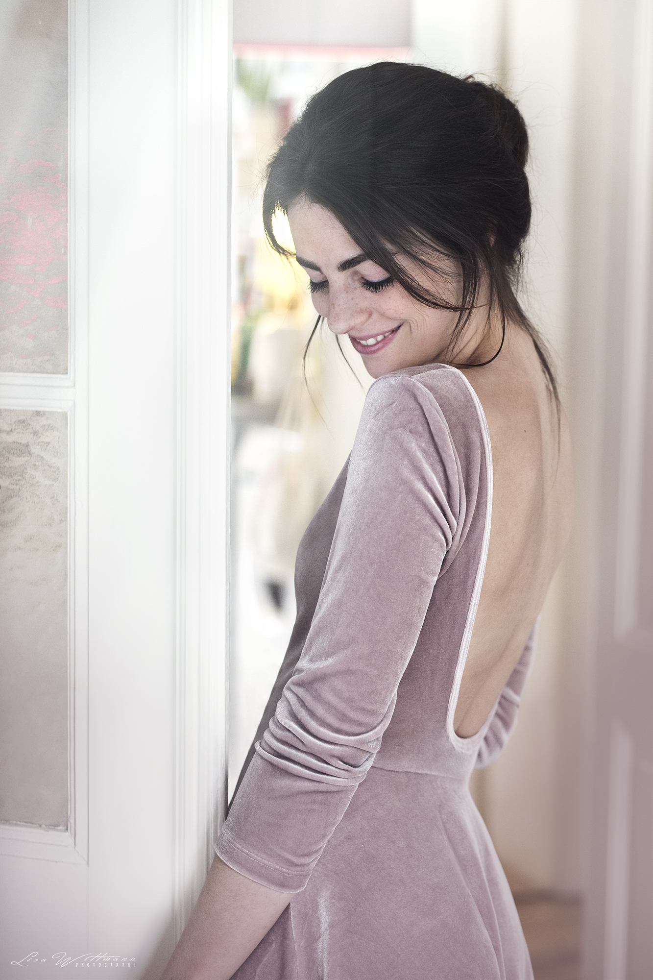 lisa_wittmann_photography_woman_backless_dress_window_laugh_beautiful_freckles_apartment_flat_bun_natural_available_smile